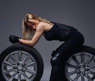 Moda, sport, ekstremum Uwodzicielska rowerzysta dziewczyna jest ubranym motocykl przekładnię pozuje z samochodowym toczy wewnątrz fotografia royalty free