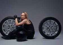 Moda, sport, ekstremum Uwodzicielska rowerzysta dziewczyna jest ubranym motocykl przekładnię pozuje z samochodowym toczy wewnątrz obraz stock