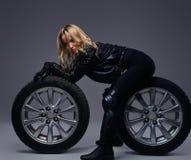 Moda, sport, ekstremum Zmysłowa rowerzysta dziewczyna jest ubranym motocykl przekładnię pozuje z samochodowym toczy wewnątrz stud zdjęcia stock