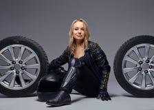 Moda, sport, ekstremum Zmys?owa rowerzysta dziewczyna jest ubranym motocykl przek?adni obsiadanie na pod?odze z samochodowym tocz zdjęcia royalty free