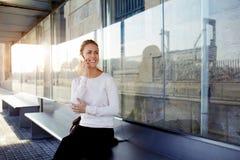 Młoda szczęśliwa kobieta opowiada na telefonie komórkowym z jej chłopakiem podczas gdy ona czekanie dla taxi na staci, Obraz Royalty Free