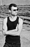 Moda tirada: retrato del hombre joven hermoso en gafas de sol que llevan de la camisa negra. Blanco y negro Imágenes de archivo libres de regalías