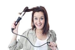Młoda uśmiechnięta dziewczyna używa fryzowania żelazo Zdjęcie Royalty Free