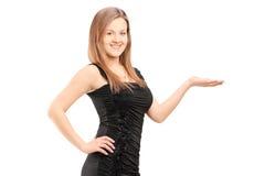 Młoda uśmiechnięta kobieta gestykuluje z ręką w sukni Obraz Stock