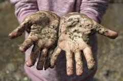 Modderige handen door de rivier Stock Foto