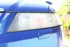 Modderige koplamp op de voorzijde van de auto die het oppoetsen vereisen stock foto