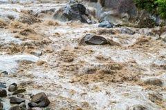 Modderige waterstroom snel in Urubamba-Rivier in Aguas Calientes stock foto's