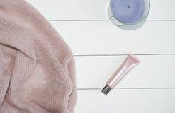 Mode étendue plate sur le fond, les vêtements de rose de vue supérieure, cosmétiques en bois blancs et avec la bougie photo stock