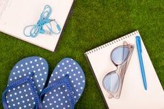 Mode-Accessoires - Flipflops, Buch, Notizblock, Stift, Kopfhörer, Notizblock, Sonnenbrille auf dem Gras Lizenzfreie Stockfotografie