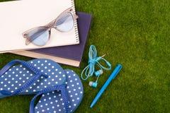 Mode-Accessoires - Flipflops, Buch, Notizblock, Stift, Kopfhörer, Notizblock, Sonnenbrille auf dem Gras Lizenzfreie Stockfotos