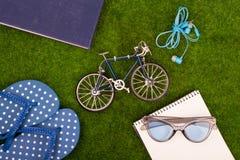 Mode-Accessoires - Flipflops, Buch, Notizblock, Stift, Kopfhörer, Notizblock, Sonnenbrille, Spielzeugfahrrad auf dem Gras Stockbild
