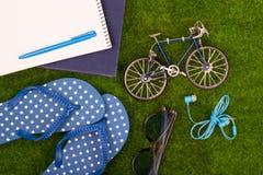 Mode-Accessoires - Flipflops, Buch, Notizblock, Stift, Kopfhörer, Notizblock, Sonnenbrille, Spielzeugfahrrad auf dem Gras Stockfotografie