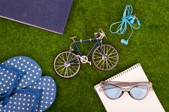 Mode-Accessoires - Flipflops, Buch, Notizblock, Stift, Kopfhörer, Notizblock, Sonnenbrille, Spielzeugfahrrad auf dem Gras Lizenzfreie Stockfotos