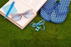 Mode-Accessoires - Flipflops, Buch, Stift, Kopfhörer, Notizblock, Sonnenbrille auf dem Gras Lizenzfreie Stockbilder