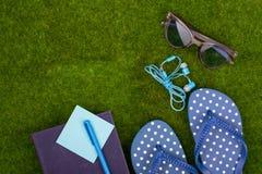 Mode-Accessoires - Flipflops, Buch, Stift, Kopfhörer, Notizblock, Sonnenbrille auf dem Gras Stockbild