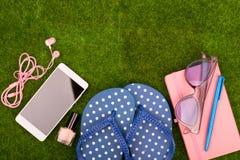 Mode-Accessoires - Flipflops, intelligentes Telefon mit Kopfhörern, Notizblock, Sonnenbrille auf dem Gras Stockbild