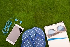 Mode-Accessoires - Flipflops, intelligentes Telefon mit Kopfhörern, Notizblock, Sonnenbrille auf dem Gras Stockfotos