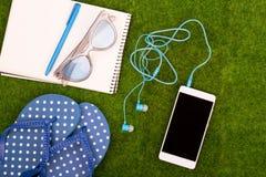 Mode-Accessoires - Flipflops, intelligentes Telefon mit Kopfhörern, Notizblock, Sonnenbrille auf dem Gras Stockbilder
