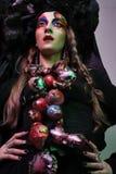 Mode, beauté, les gens et concept de Halloween : Jeune femme avec un maquillage créatif lumineux et une grande coiffe noire image libre de droits