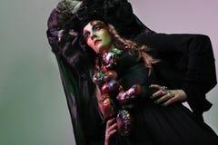 Mode, beauté, les gens et concept de Halloween : Jeune femme avec un maquillage créatif lumineux et une grande coiffe noire image stock