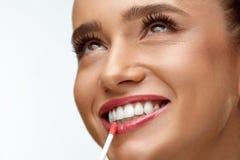 Mode With Beauty Face modèle féminin appliquant le baume à lèvres sur des lèvres photos stock