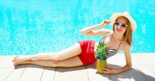 Mode, begrepp för sommarferier - kvinna som ligger med ananas och solglasögon på en pöl för blått vatten arkivfoton