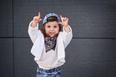 Mode behandla som ett barn flickahöftflygtur lite flicka i en baseballmössa Royaltyfri Foto