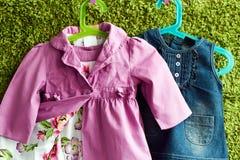 Mode behandla som ett barn klänningen och laget som hänger på en hängare på en grön sommarbakgrund Royaltyfri Fotografi