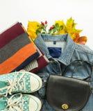 Mode d'automne, équipement d'automne de femme sur le fond blanc Veste bleue de denim, sac crossbody noir, espadrilles de point de Photographie stock libre de droits