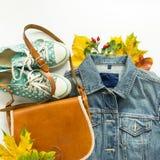 Mode d'automne, équipement d'automne de femme sur le fond blanc Veste bleue de denim, sac crossbody rouge, espadrilles de point d Image stock