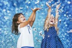 Mode d'enfant de deux petites filles avec les confettis argentés dans le backg Photographie stock
