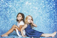 Mode d'enfant de deux petites filles avec les confettis argentés dans le backg Photo stock