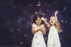 Mode d'enfant de deux petites filles avec les confettis argentés dans le backg Photo libre de droits