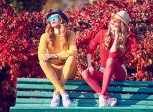Mode de chute Jeune femme s'asseyant sur le banc Photo stock