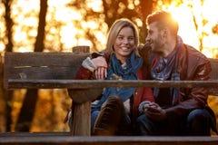 Mode de vie, amie heureuse et ami sur le banc en parc Photographie stock