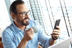 Mode de vie d'affaires Commerçant en verres se reposant au café avec du café potable d'ordinateur portable vérifiant l'appli marc photo stock