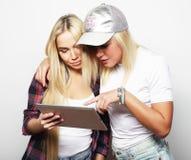 Mode de vie et concept de personnes : deux amies de hippie avec le comprimé numérique Photo stock