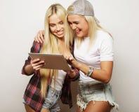 Mode de vie et concept de personnes : deux amies de hippie avec le comprimé numérique, tir de studio Photo stock