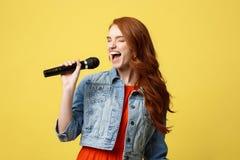 Mode de vie et concept de personnes : Fille expressive chantant avec un microphone, fond jaune lumineux d'isolement Image stock