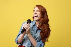 Mode de vie et concept de personnes : Fille expressive chantant avec un microphone, fond jaune lumineux d'isolement Photo libre de droits