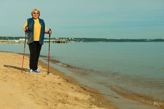 Mode de vie mûr actif marche nordique supérieure sur une plage sablonneuse Images stock