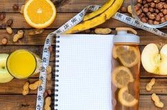 Mode de vie sain ; bouteille de forme physique ; porte des fruits les oranges ; pommes et bananes ; noisettes et arachides ; jus  Photo stock