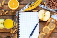 Mode de vie sain ; bouteille de forme physique ; porte des fruits les oranges ; pommes et bananes ; noisettes et arachides ; jus  Photos stock