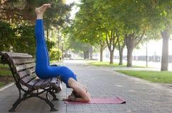 Mode de vie sain en nature, femme faisant l'exercice de yoga sur le tapis en parc photographie stock libre de droits