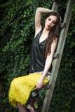 Mode in der jungen Frau des Gartens im eleganten gelben Rock und im Schwarzen lizenzfreie stockbilder