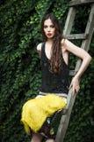 Mode in der jungen Frau des Gartens im eleganten gelben Rock und im Schwarzen stockfoto