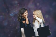 Mode der kleinen Mädchen Kindermit Papiertüten auf einem Hintergrund mit Lizenzfreies Stockfoto