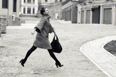 Mode et concept de personnes - jeune femme ou adolescente heureuse courant et sautant haut sur la rue de ville Photographie stock libre de droits
