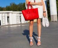 Mode et style La fille aux longues jambes se tient en parc une soirée d'été dans une robe et une exploitation blanches courtes de Photo libre de droits