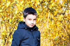 Mode för barn` s kläder för höstbarn` s en pojke i ett svart omslag på en gul bakgrund Informell stil arkivfoton
